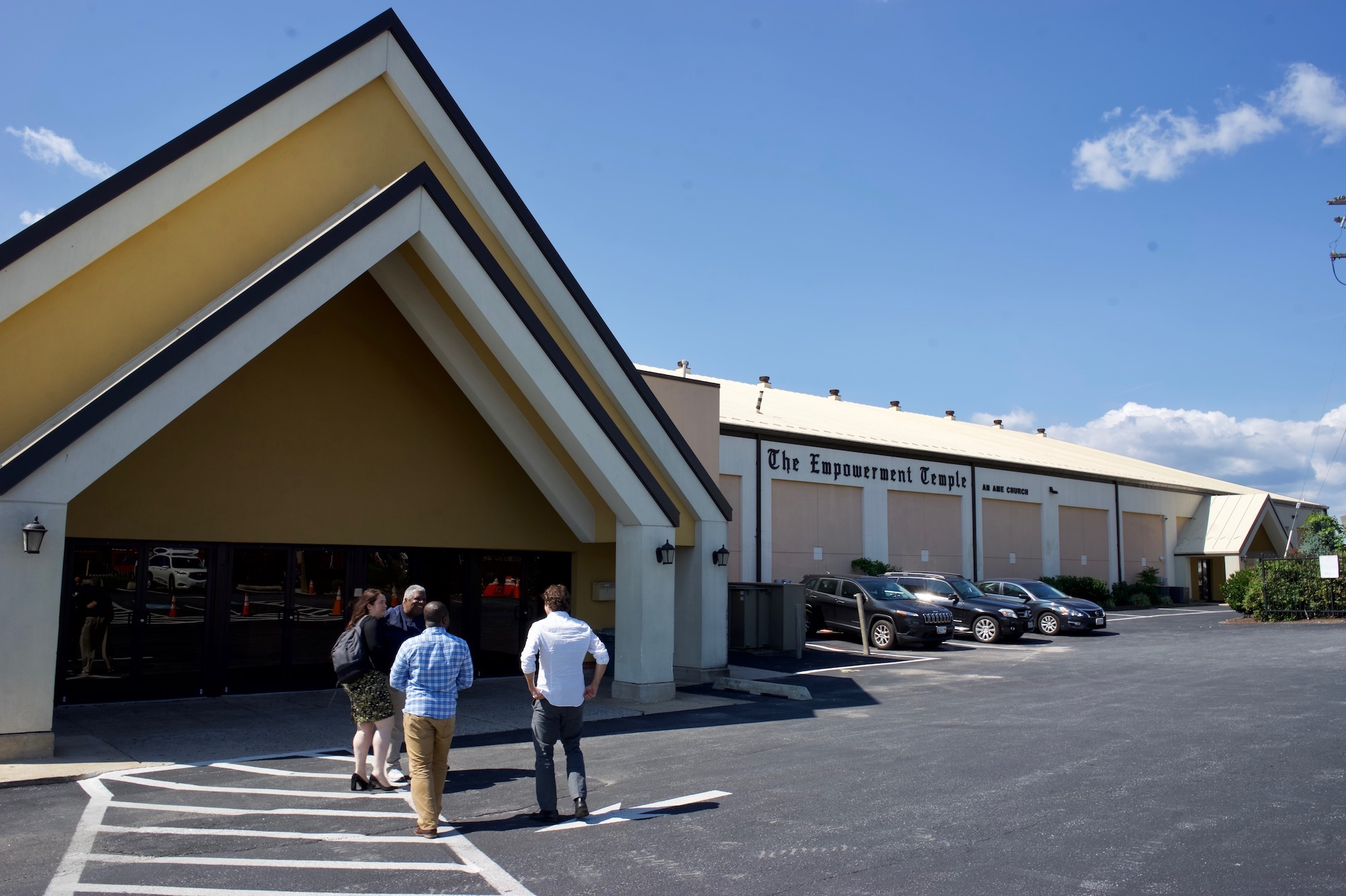 A large angled arch of a building in front of a large parking lot. On the body of the building it reads